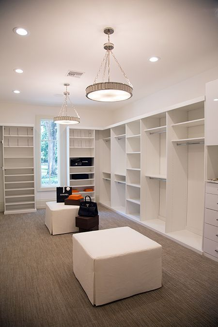 Transitional walk-in closet features two nickel disc pendants, Hudson Valley Lighting Lynden Pendant, illuminating white modular storage systems alongside a pair of matching white skirted ottomans atop a wall to wall taupe rug.