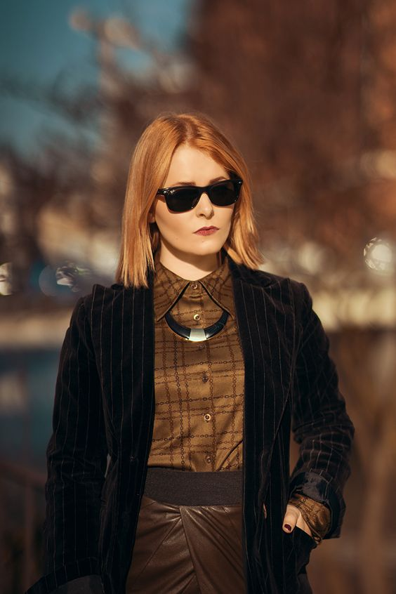 Christina Key is wearing a black ray ban sunglasses and a chic retro blouse