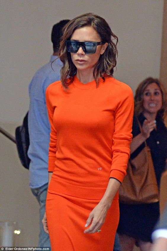 The morning after: Victoria Beckham looked a tad jaded as she left her hotel wearing personalised orange dress and very dark sunglasses following tipsy NYFW celebrations