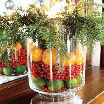 Create an Arrangement with Fruit and Greenery  Use a glass hurricane or vase to create an arrangement that will last throughout the Christmas season by filling the jar with a layer of limes, red holly berries, and lemons. Top it off with stems of greenery