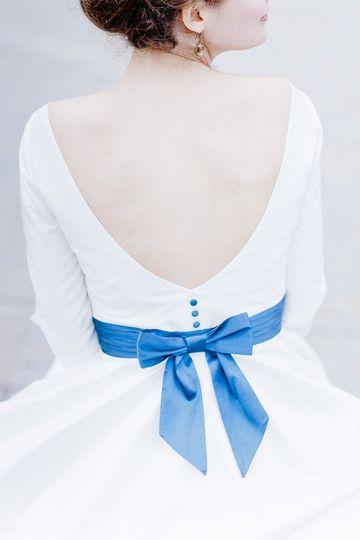 Brautkleid mit tiefem Rückendekolleté und breitem, blauen Gürtel mit Schleife und Knöpfen, vorne U-Bootausschnitt, lange Arme mit Manschette, tea- length Tellerrock mit Petticoat