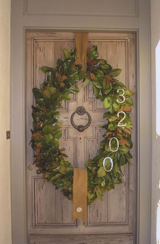 Oval magnolia wreath with address numbers. This could be re-created with our oval work wreath form. #christmaswreath #ovalwreath #frontdoor