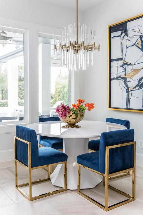 A Round White Dining Table Finished With Gold And Blue Sapphire Dining Chairs Under A Brass Modern Dining Room Dining Room Inspiration Dining Room Paint Colors