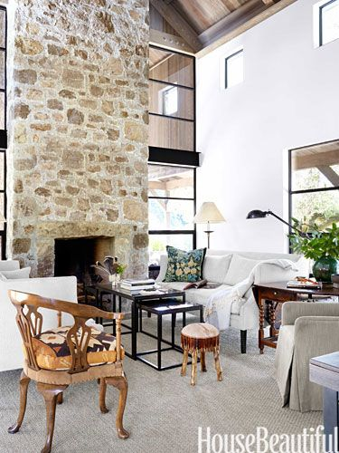 The seating area in the living room of this Sonoma, California, house is focused on a massive fireplace made of local stone.