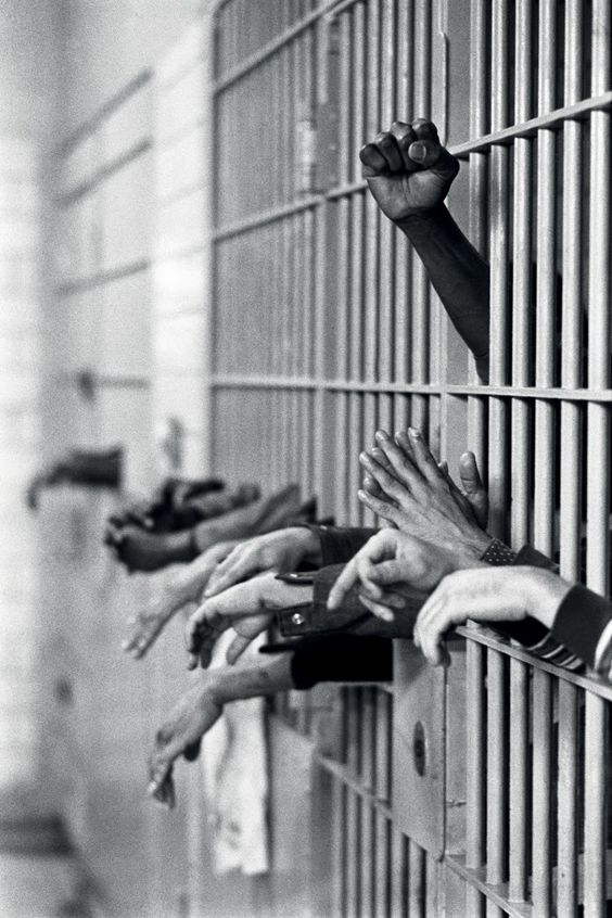 Photojournalism - A fist raised in protest from behind the bars at Toms Prison, Manhattan, on 28 September, 1972. Legendary photojournalist Jean-Pierre Laffont captured the changing times of New York City, covering everything from free love to the grim and gritty '70s.: