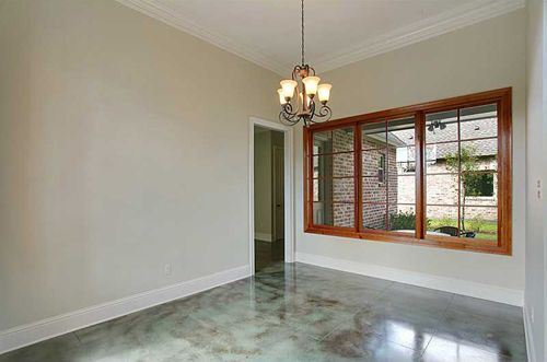 Formal dining room with wall of picture windows and stained concrete flooring.