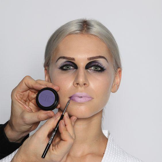 """Step 15: Lippenkontur  Mit einem kleinen, abgeschrägten Konturenpinsel zunächst die Mundwinkel mit einem fliederfarbenen Lidschatten (""""Pflaume"""") und anschließend in den äußersten Ecken mit schwarzem Lidschatten (""""Lakritze"""") eindunkeln. Der Lidschatten haftet auf der cremigen Lippenfarbe sehr gut. Durch die eingedunkelten Ecken  erscheinen die Lippen dreidimensional – ein sehr interessanter Effekt für ein ultra-modernes Lippen-Make-up."""