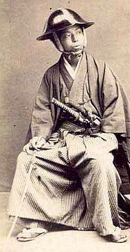 Samurai wearing a jingasa and holding a muchi (whip).