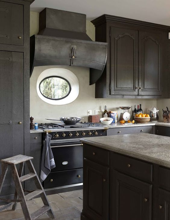 In an architect's home in the Flemish countryside, a gunmetal-gray kitchen with a curiously-shaped stove hood.