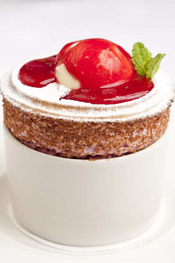 Raspberry soufflé is a fixture on many menus, but the addition of a buttermilk ice cream and a sprightly coulis by George Blogg distinguishes this version from the competition. Pour the coulis at the table for maximum impact.