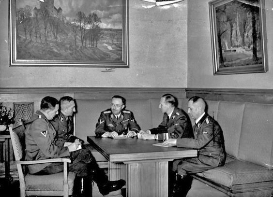 1939 photograph; shown from left to right are Franz Josef Huber, Arthur Nebe, Heinrich Himmler, Reinhard Heydrich and Heinrich Müller, planning the investigation of the bomb assassination attempt on Adolf Hitler of 8 November 1939 in Munich. - Bundesarchiv CC-BY-SA 3.0
