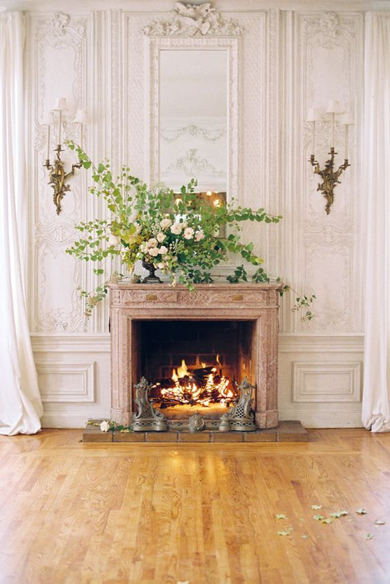 Inspiration from Paris apartment interior design ideas - a charming living room with stone fireplace and paneled walls with ornate brass sconces and a magnificent floral arrangement.