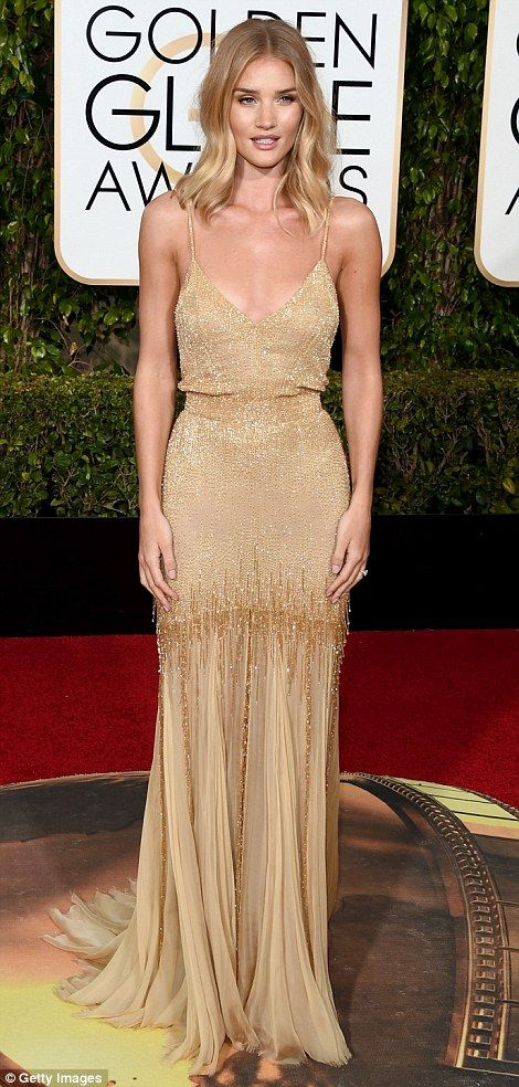 Golden girls: Newly engaged Rosie Huntington-Whiteley (left, in Atelier Versace) and Eva Green (wearing Elie Saab) shimmered in the spotlight thanks to delicate gold gowns