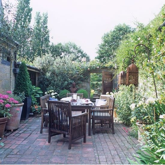 A secluded terrace makes a lovely spot for alfresco dining, while a large wooden table and chairs provides plenty of seating for family and guests.