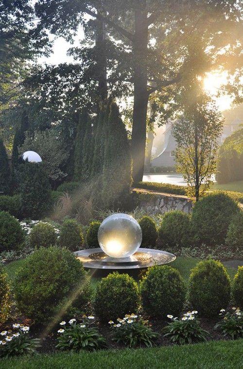 Kulista fontanna w pięknym, zielonym ogrodzie