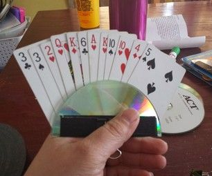 Playing Card Holder - cut an old CD slightly off center (so back of holder will end up being slightly higher than front, making it easier to slide cards in), tape together with duct tape, then secure with a binder clip. Genius!