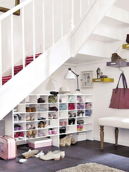 Bei einer Treppe im Flur sollten Sie den Platz darunter für ein Regal nutzen. In unserem Beispiel sind Pullover, Taschen, Schuhe darin zur dekorativen Bildwand arrangiert. Auf dem obersten Bord ist Platz für Hüte, Schals und eine Tischleuchte. Wem das zu bunt im Flur wird, der kann die Regalfront auch mit Faltrollos schließen.