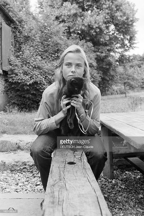 Rendezvous With Margaux Hemingway. En France, le 20 juin 1980, Margaux HEMINGWAY, l'actrice et petite-fille d'Ernest Hemingway, souriante, assise sur une table de jardin, tenant un chat, dans la maison de l'écrivain américain Mark Princi, à Fontainebleau. .: