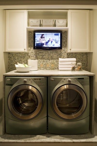 front loading washer & dryer with built in cabinet over them makes a great folding area, small flatscreen TV mounted on tile wall, white painted cabinets, glass bottles for storage, French metal bins with pulls on open shelving
