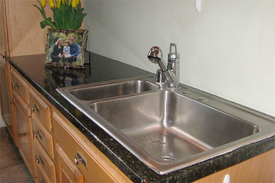 Faux granite film to cover an existing countertop to look like granite.  Appliance Art or EZ Faux on-line.  Looks good.