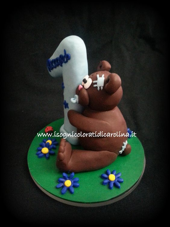Un tenero orsacchiotto da mettere su una torta di compleanno. Realizzato a mano in paste sintetiche, base in plexiglass. Personalizzabile.