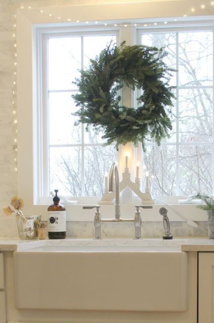Farmhouse Christmas decor in my kitchen with fresh wreath and fairy light over a farm sink. Hello Lovely Studio. #farmhousechristmas #christmasdecor #farmsink #freshwreath