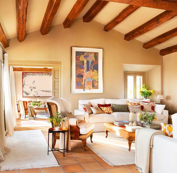 Salón en tonos beige con pinturas abstractas y vigas vistas en el techo