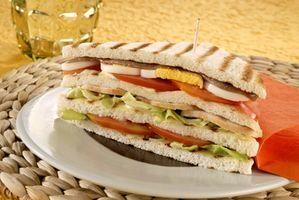 [Club sandwich] Ricetta per 2 persone: 4 fette di pancarrè per tramezzini; 200 g circa  di petto di pollo; 2 uova; 4 filetti di acciuga sott'olio; 1 pomodoro  maturo ma sodo; qualche foglia di lattuga; 2 cucchiai di maionese;  olio extravergine d'oliva; vino bianco; 2 foglie di salvia; sale e  pepe.