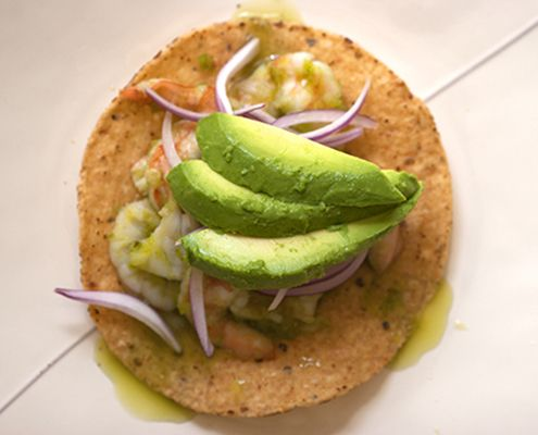 Camarones en aguachile is made from serrano chiles blended with lime juice, giving the dish intense heat and fresh chile flavor.