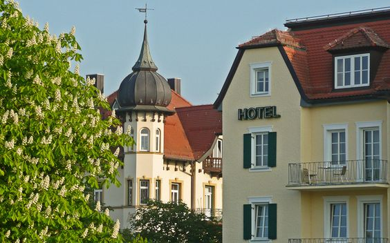 Blühende Kastanie vor einem Hotel in Starnberg. Einige Hotels und Ferienwohnungen am Starnberger See liegen direkt am See.