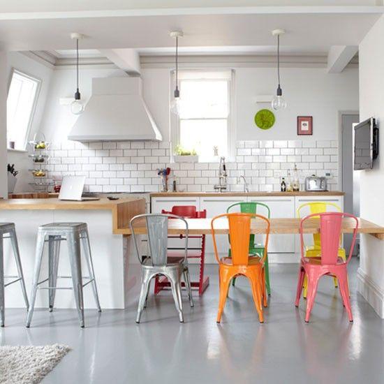 Belle idée, la table repas dans le prolongement du plan de travail de la cuisine. Les murs sont très sobres, les chaises multicolores apportent un vrai plus.