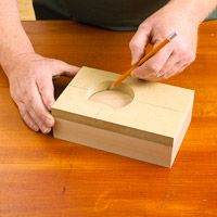 1. Mark the workpiece  Using pencil on inside of hole Cut an MDF or hardboard template to the desired hole shape using a jigsaw, scroll saw, or circle cutter. Sand sawn edges smooth. Now, hold the template on the workpiece and mark the hole location as shown.