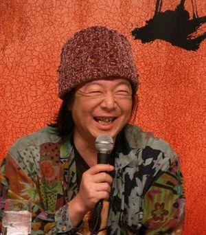 赤いニットの帽子をかぶってマイクを持っている古田新太の画像