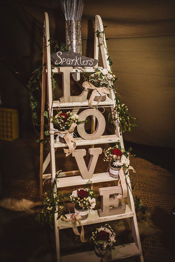 Vintage step ladder display with wooden LOVE letters sparkler bucket & jars filled with flowers - Lola Rose Photography - A Winter Wedding in a Tipi with Lace Fishtail Annasul Y Wedding Dress, Jenny Packham Headpiece & Rachel Simpson Shoes. Bridesmaids wear Red Dresses & Cream Fur Stole's and Groomsmen in Traditional Morning Suits.: