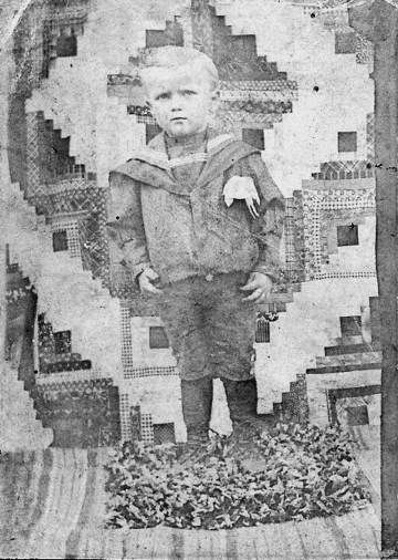 Carl Martin, my grandfather, posing in front of a Log Cabin Barn Raising quilt around 1900. Apparently, Log Cabin quilts run in my blood. --Judy Martin: