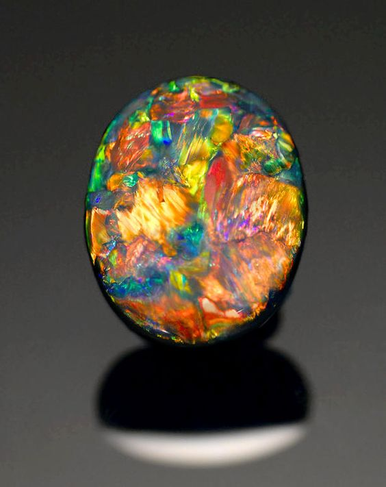 "Very Fine Black Opal from Lightning Ridge, Australia.  Vivid and very ""present"", this fine gem opal displays predominantly red play-of-color with spectral broad flashes of green, orange, yellow and blue, with true black potch to the reverse of the oval cabochon. This is as fine a stone for the serious collector as can be desired.  Weighing approximately 10.39 carats and measuring 16.5 x 13.0 x 6.5mm Estimate: US$ 60,000 - 80,000 (£39,000 - 52,000/€46,000 - 62,000)"