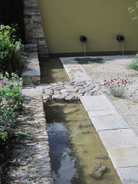 I like the way the stone path looks to be sitting loose as a bridge through water feature. Great use of materials blending together