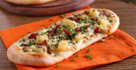 Dinnede: pizzette speciali di pasta di pane con una farcitura molto golosa con crema di panna, patate, speck, cipolla, formaggio ed erba cipollina.