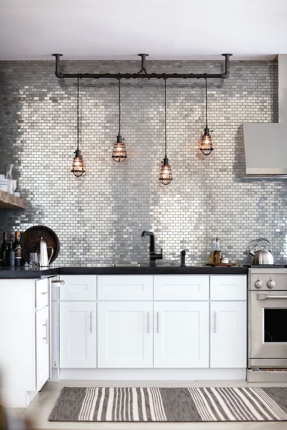 Such a cool kitchen … stainless metal mosaic tiles, aged bronze cage pendant lights, an adjoining...: