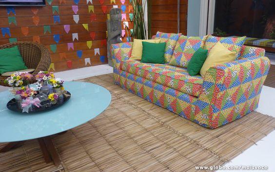Além das bandeirinhas, o tapete de palha e o sofá estampado deixam a sala no clima: