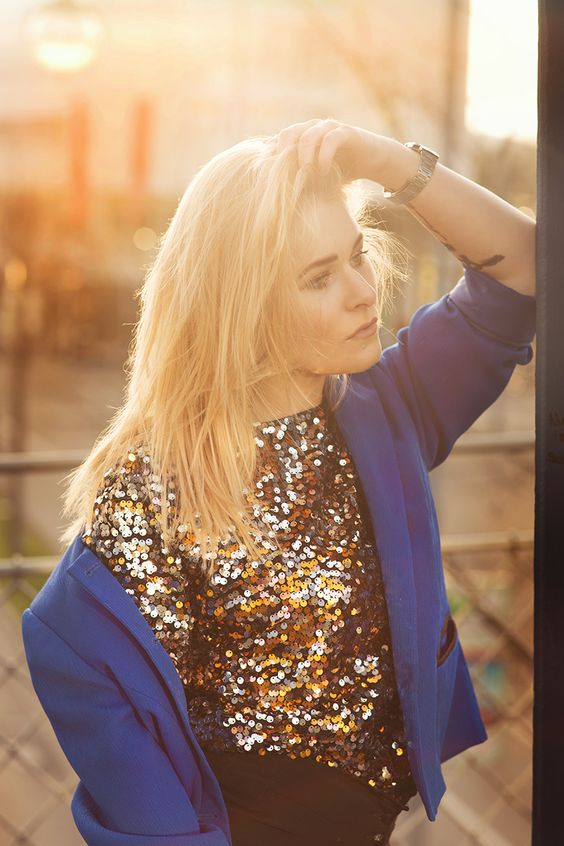 Christina Key is wearing a goldne shirt and a blue blazer