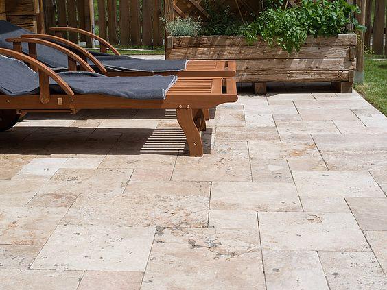 Terrasse rustique en dalles de travertin avec des chaises longues en bois