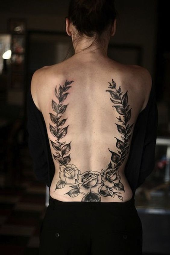 Rose and leaves lower back tattoo.