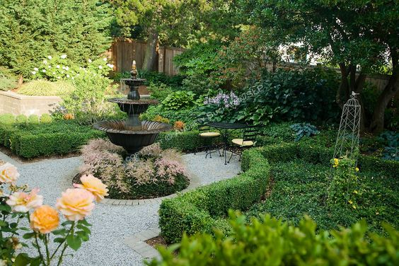 a formal backyard garden edged with roses framed by