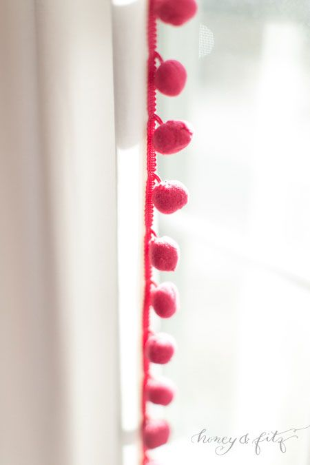 Add pom-pom trim to a plain, store-bought window panel for a fun accent! #DIY