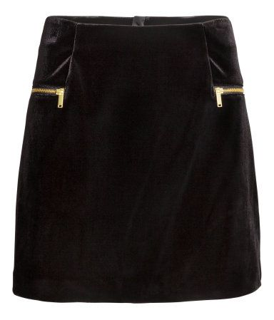 Black. Short velvet skirt. Mock front pockets with decorative zips. Visible zip at back. Unlined.