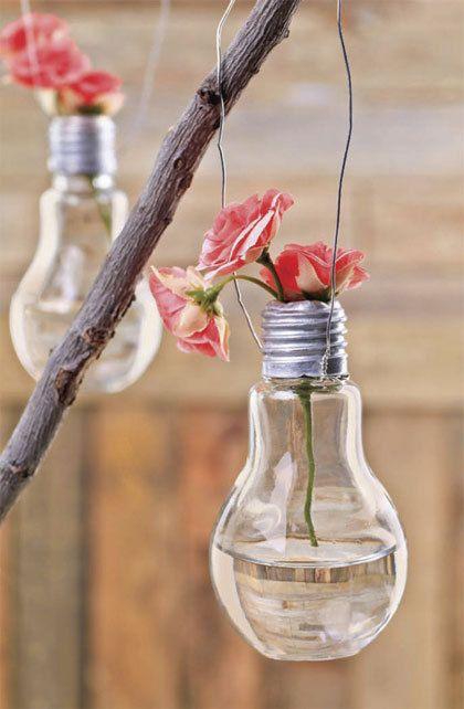 romantisch detail: 1. doe de handschoen aan de hand waarmee je de lamp vasthoud. Houd de lamp altijd vast aan de fitting en niet aan het glas, anders kan het breken.  2.Verwijder het dunne zilveren laagje van de onderkant met het tangetje.  3.Verwijder vervolgens het zwarte kapje zodat de tang in de gloeilamp kan.  4.Trek het lampje en de draden uit de glazen bol.  5.Wikkel het ijzerdraad om de fitting en maak er een hanger van. 6.Doe er water in en wat bloemen of takken met groen blad.