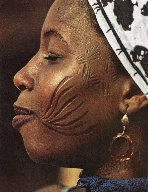 Mulher Nigeriana com o orgulho escarificado //  (A prática da escarificação e da pintura corporal atinge patamares sofisticadíssimos. Para eles, a escarificação é um atestado de bravura. Um guerreiro não pode ostentar nenhuma cicatriz até que tenha matado um inimigo. Para uma mulher, as cicatrizes são uma maneira de ficar atrativas para os homens. As escarificações são feitas com facas, pedras ou pregos. Depois a ferida é coberta com cinzas.civilizacoesafricanas.blogspot.com.br)