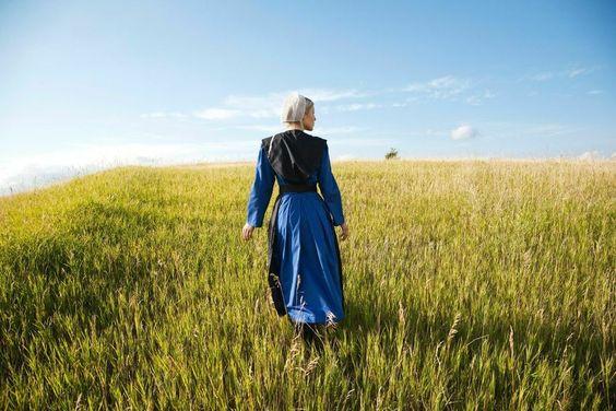 Kunstwerk: 'Amish woman in blue dress and black cape in field' van Hollandse Hoogte