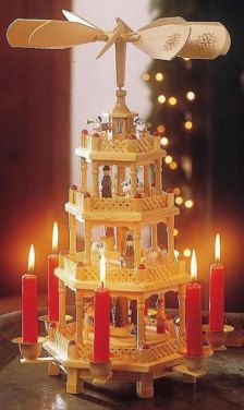 """Christmas pyramid Weihnachtspyramide: Originally from the Erzgebirge region of Germany, the wood or rope pyramid was the """"poor man's Christmas tree."""" Today it is a popular Christmas decoration in many parts of Germany, usually made with candles and bells that ring as the heat from the candles turns a wooden rotor at the top."""